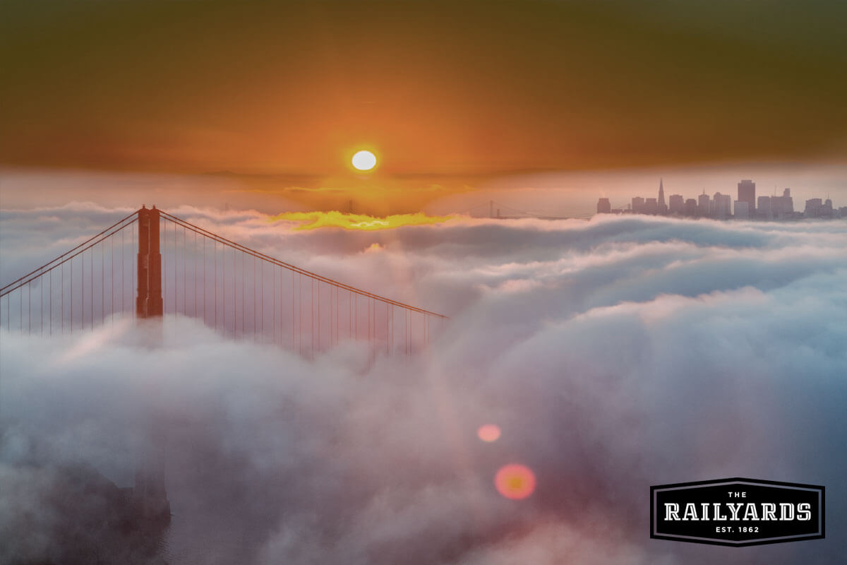 The Golden Gate Bridge rising out of early morning fog. Discover 4 historical stops to include on your next CA road trip.