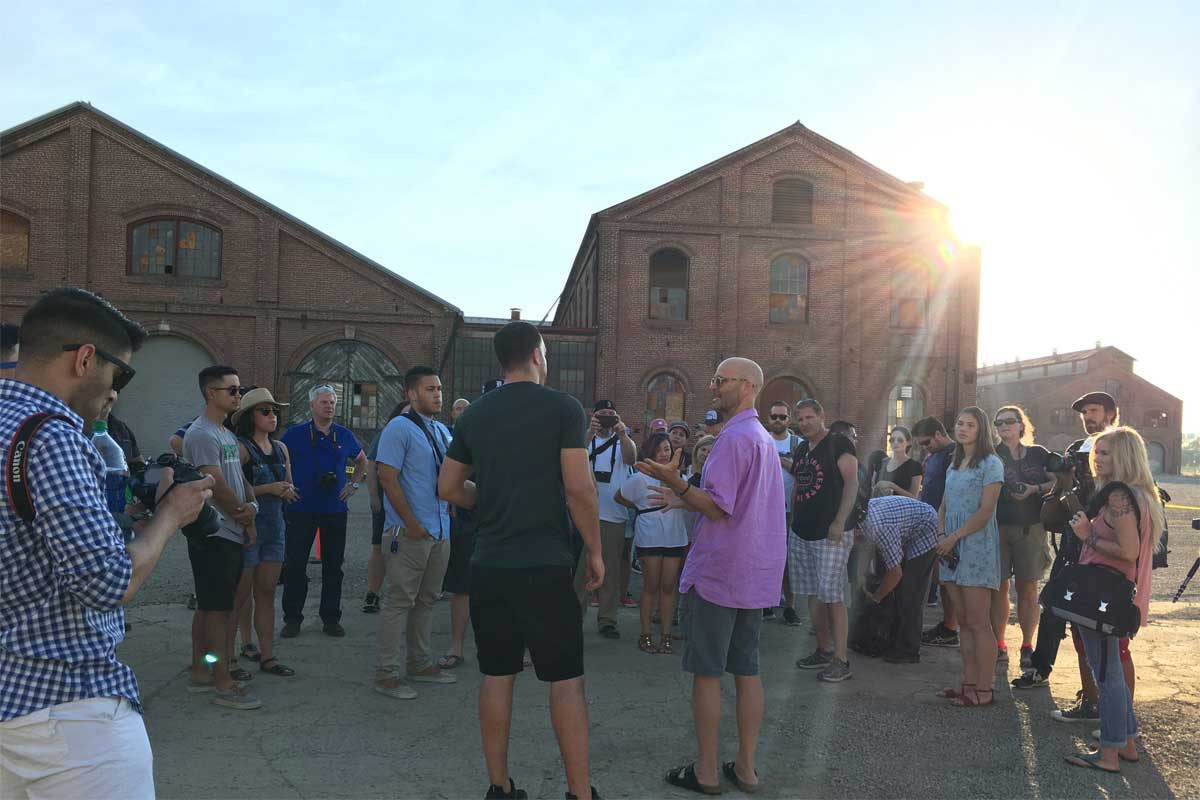 An image of a group of people gathered in front of the Railyards' historic buildings. Learn more the plans for housing at the Railyards.