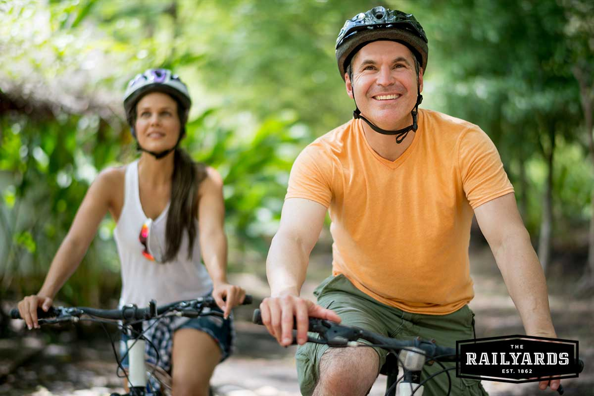 A couple biking in Sacramento. Discover 5 ways to celebrate bike month in Sacramento at the Railyards.com